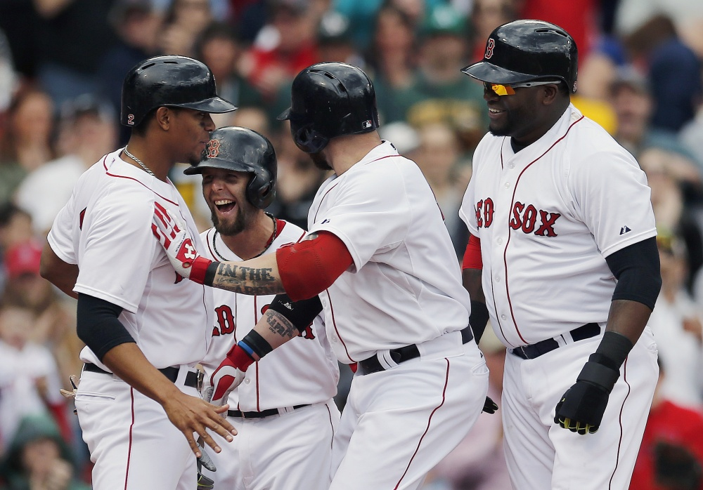 Boston Red Sox's Jonny Gomes, center, celebrates his grand slam that also drove in, from left, Xander Bogaerts, Dustin Pedroia and David Ortiz in the first inning against the Oakland Athletics in Boston on Saturday.