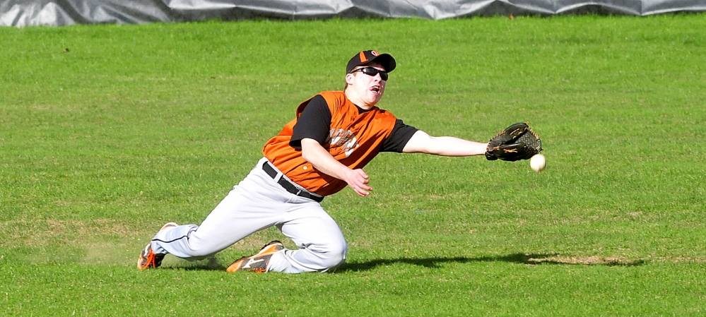 Staff photo by David Leaming Gardiner's Josh Ferrin reaches for fly ball in center field during game against Waterville on Monday, May 5, 2014.