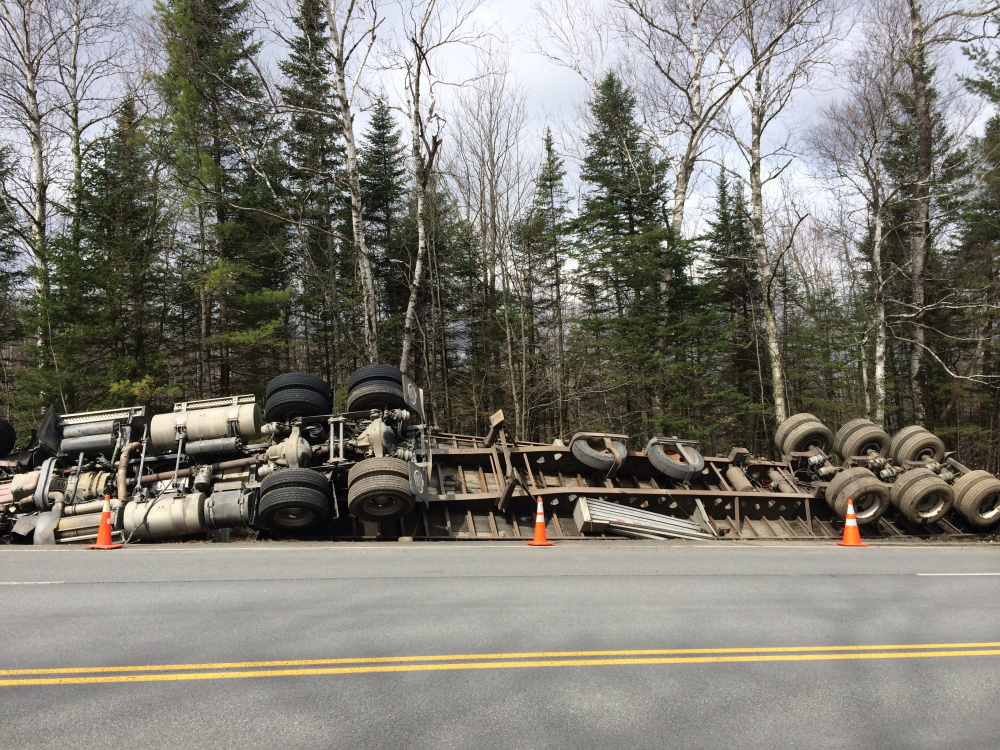 On its side: A tractor-trailer truck rests on its side Monday morning on U.S. Route 201 in Solon. The driver wasn't hurt when the truck, carrying lumber and owned by a Quebec company, caught mud at the side of the road, causing it to tip.