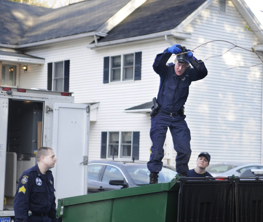Death Investigation: State Police Detective Terry James, center, photographs the interior of a Dumpster Monday outside of the apartment that Leroy Smith II shared with his son, Leroy Smith, in South Gardiner. Detective Sgt. Jason Richards, left, and Trooper Breanne Petrini searched the Dumpster in the evening after the elder Smith's body was recovered in Richmond.