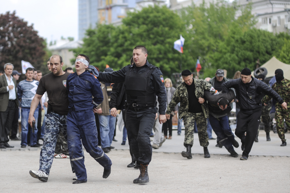 Pro-Russian activists convey captured fire service employees to the regional administration building in the city of Donetsk, in eastern Ukraine, on Monday. Pro-Russian forces and their supporters have been seizing and ransacking government buildings across eastern Ukraine amid a mounting anti-government insurgency that is threatening to tip the former Soviet nation into widespread civil conflict.