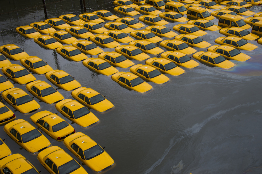 In this Oct. 30, 2012 file photo, a parking lot full of yellow cabs in Hoboken, N.J. is flooded as a result of Superstorm Sandy. Global warming is rapidly turning America the beautiful into America the stormy, sneezy and dangerous, according to the National Climate Assessment report released Tuesday, May 6, 2014.
