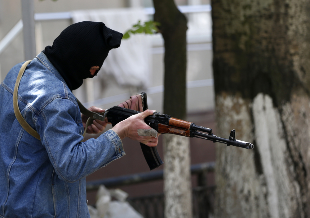 A pro-Russian gunman holds his weapon while guarding the local administration building in the center of Slovyansk, eastern Ukraine, Tuesday.