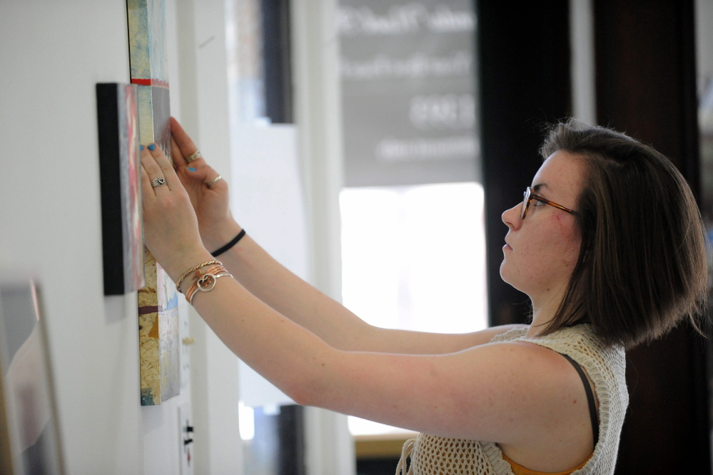 EARTH ART: Rachel McDonald, program manager at Common Street Art Gallery, hangs pieces by Readfield artist Christine Higgins at Common Street Art Gallery in downtown Waterville on Wednesday. Local artists' work will be on display starting Friday.