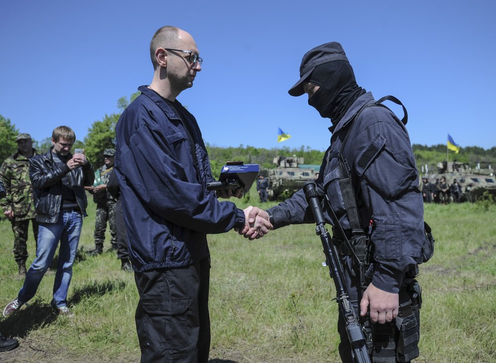 Ukrainian Prime Minister Arseniy Yatsenyuk, left, shakes hands with a Ukrainian soldier at a checkpoint in Slovyansk, Ukraine, Wednesday. Ukrainian military operations that began Monday to expunge pro-Russia forces from the city of Slovyansk have been the interim government's most ambitious effort so far to quell weeks of unrest in Ukraine's mainly Russian-speaking east.