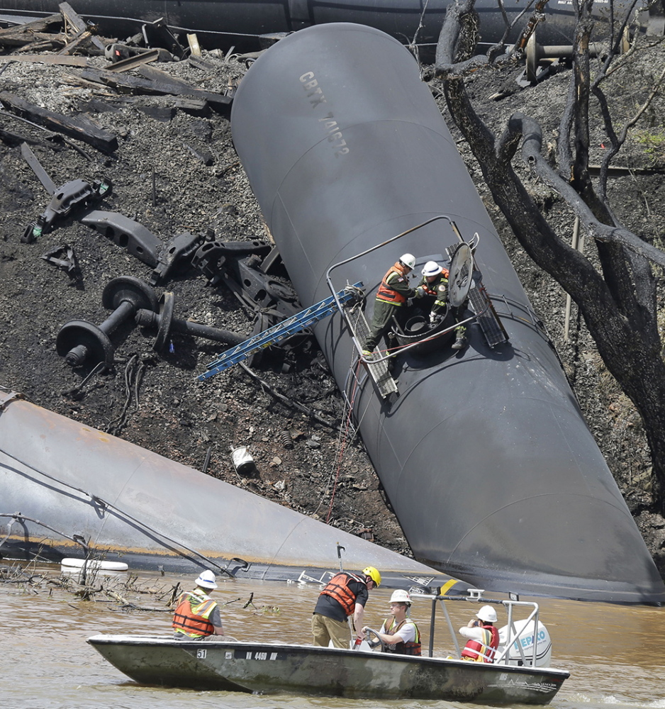 ANOTHER DERAILMENT: Workers remove damaged tanker cars along the tracks where several CSX tanker cars carrying crude oil derailed and caught fire along the James River near downtown Lynchburg, Va., on May 1.