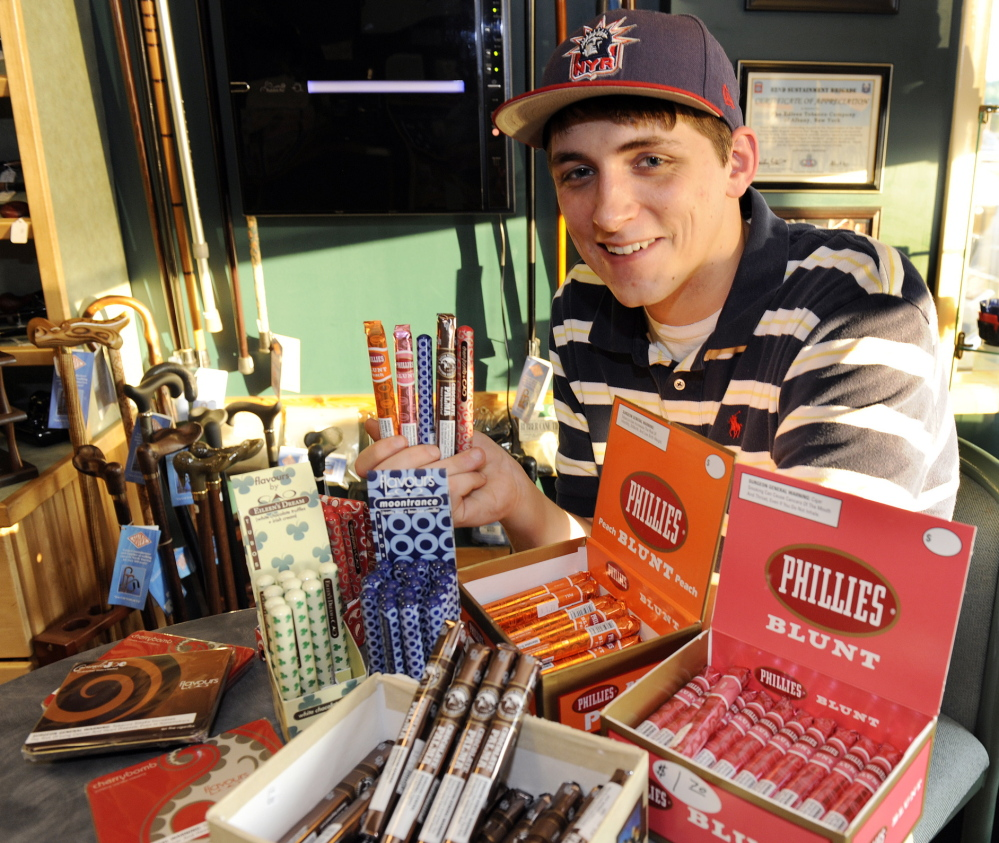 Cigar enthusiast Brendan Glennon poses with a display of candy-flavored cigars at a custom tobacco shop in Albany, N.Y., last May. Researchers at Portland State University have posted a letter in the New England Journal of Medicine stating that additives found in Jolly Rancher candies, Kool-Aid drink mixes and other sweets are being used in cigars.