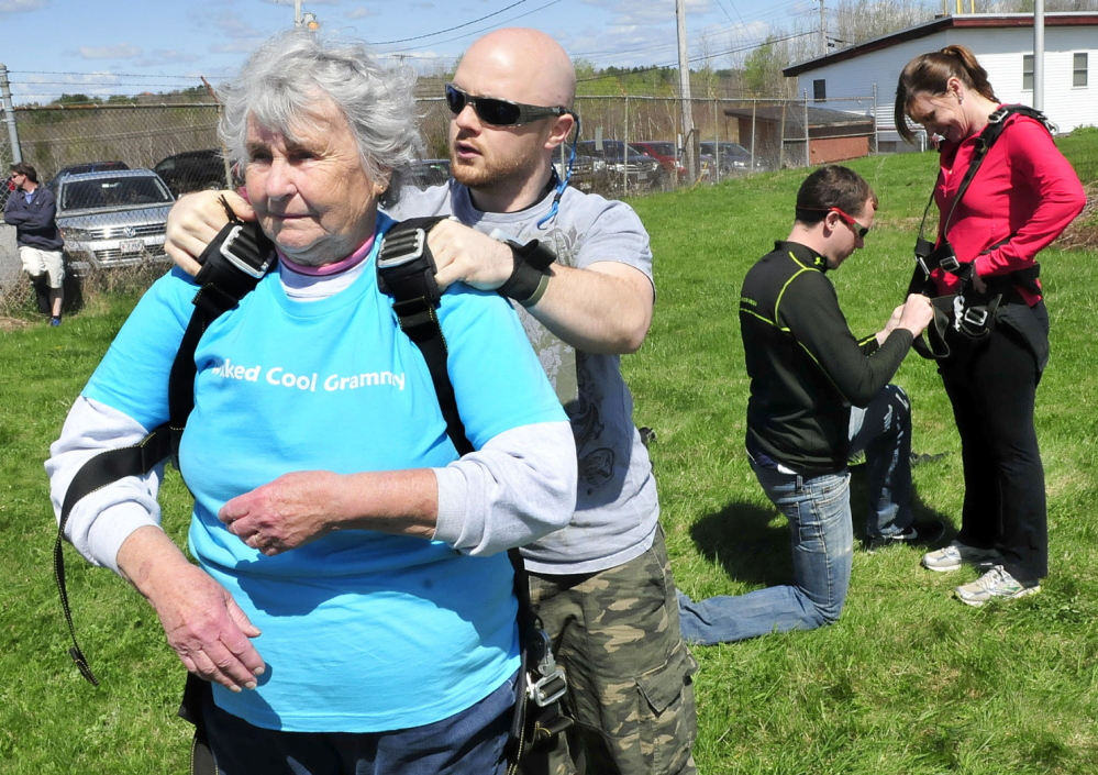 BUCKLE UP: Marjorie Bell, 80, gets buckled into a harness that she and instructor Matt Riendeau used to skydive from a plane over LaFleur Airport in Waterville on Mother's Day on Sunday, May 11, 2014. One of her daughters, Helen Bell- Necevski of Oakland, gets outfitted with a harness at right.