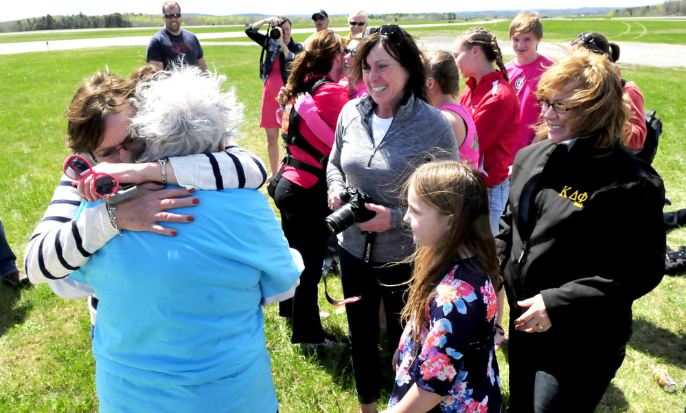 WELL DONE MA: Marjorie Bell, 80, is hugged by one of her daughters, Norma Thompson, after Bell safely landed after tandem skydiving at Lafleur airport in Waterville on Sunday, May 11, 2014. Waiting to congratulate their mother are daughters Mary Therriault, center, and Sheila Currie. Grandaughter Maggee Currie is in front.
