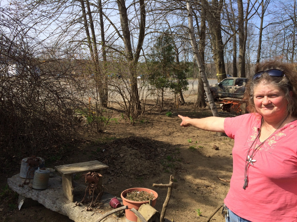 Building a fence: Lisa Ames, 55, points to the property line between her home at 52 Depot St. and the Norridgewock New Balance factory. On Thursday, the shoe manufacturer sent a letter to Ames saying they would be building a fence between the properties.