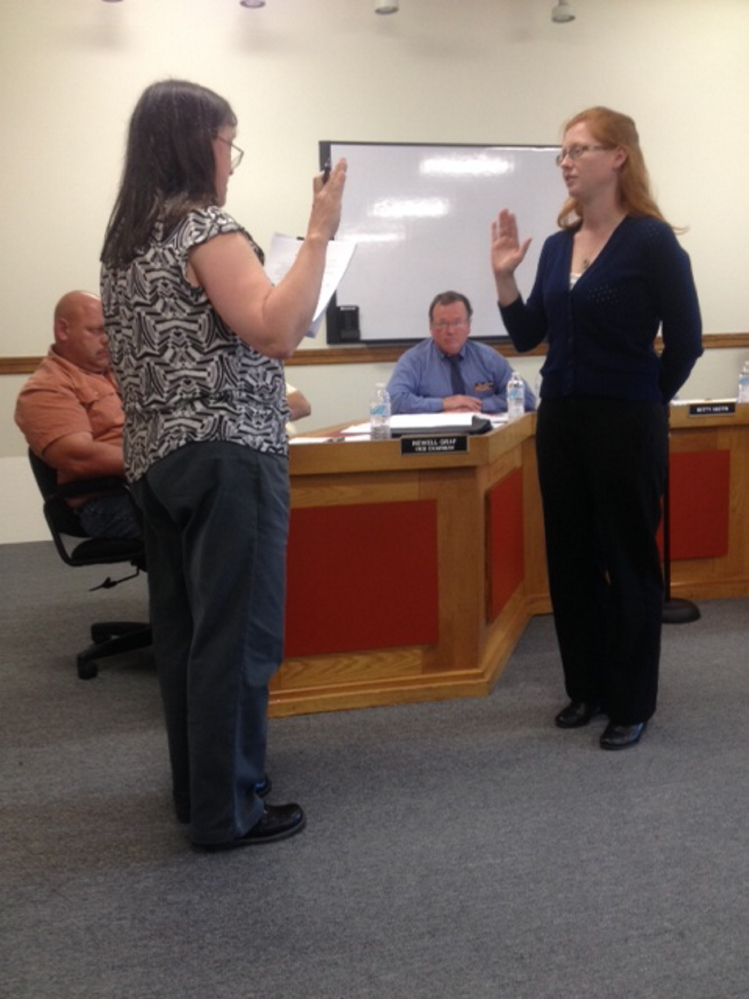 New boss: Skowhegan Town Clerk Gail Pelotte, left, administers the oath of office on Tuesday to new Town Manager Christine Almand as Skowhegan Road Commissioner Greg Dore, center, who served three months as interim town manager, watches.