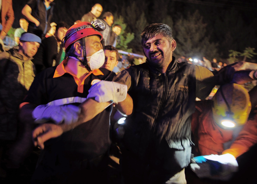 Miners help a rescued friend hours after an explosion and fire at a coal mine killed dozens and trapped others in Soma, in western Turkey, on Tuesday.