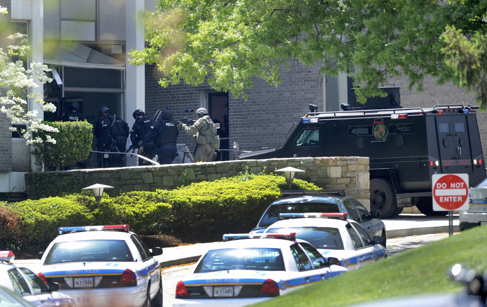 Police officers enter WMAR-TV, after a truck driven by a man rammed the Baltimore-area television station Tuesday, leaving a gaping hole in the front of the building, in Towson, Md.