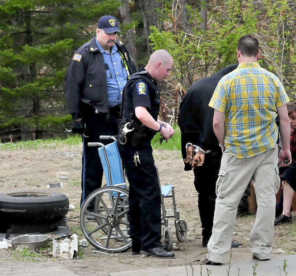 BUST: Three Skowhegan police officers including officer Ryan Dinsmore, center, place a man in handcuffs outside a home at 39 North School St. on Wednesday, following a raid by Skowhegan, Somerset County Sheriffs Office, Maine State Police and officers with the Maine Drug Enforcement Agency.