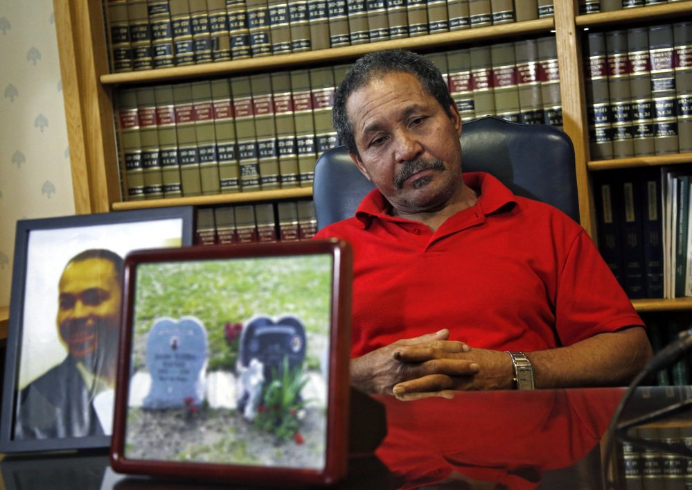 Ernesto Abreu listens during a news conference at his attorney's office in Quincy, Mass., Thursday, May 15, 2014, with photos of his son, Daniel de Abreu, and the gravesite of Daniel and Safiro Furtado. Daniel and Safiro were shot to death as they sat in a car in Boston's South End on July 16, 2012. Former Patriots star Aaron Hernandez has been indicted Thursday on new murder charges in this 2012 double slaying.