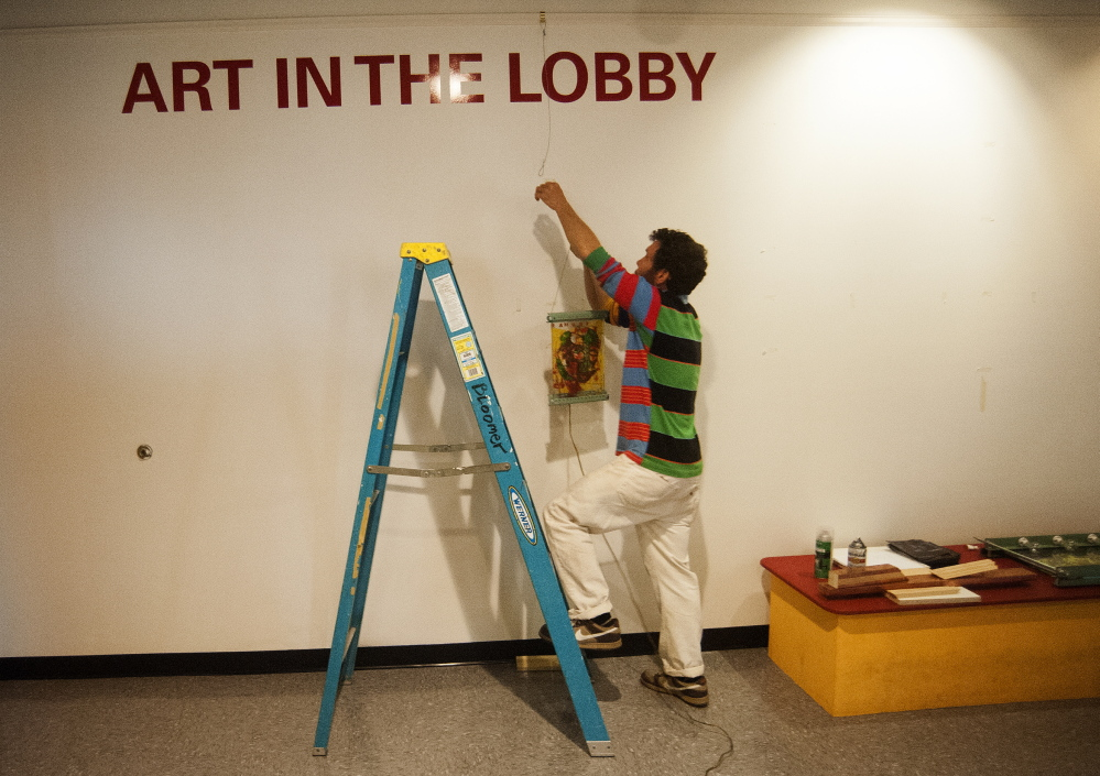 PIECES: Local artist Thom Klepach hangs pieces of his work on the new walls of the lobby at Railroad Square Cinemas in Waterville on Thursday.