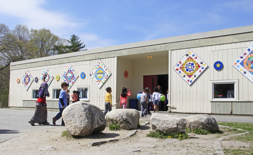 Students enter Hall Elementary School in Portland on Thursday. The school got a D grade, up from an F last year.