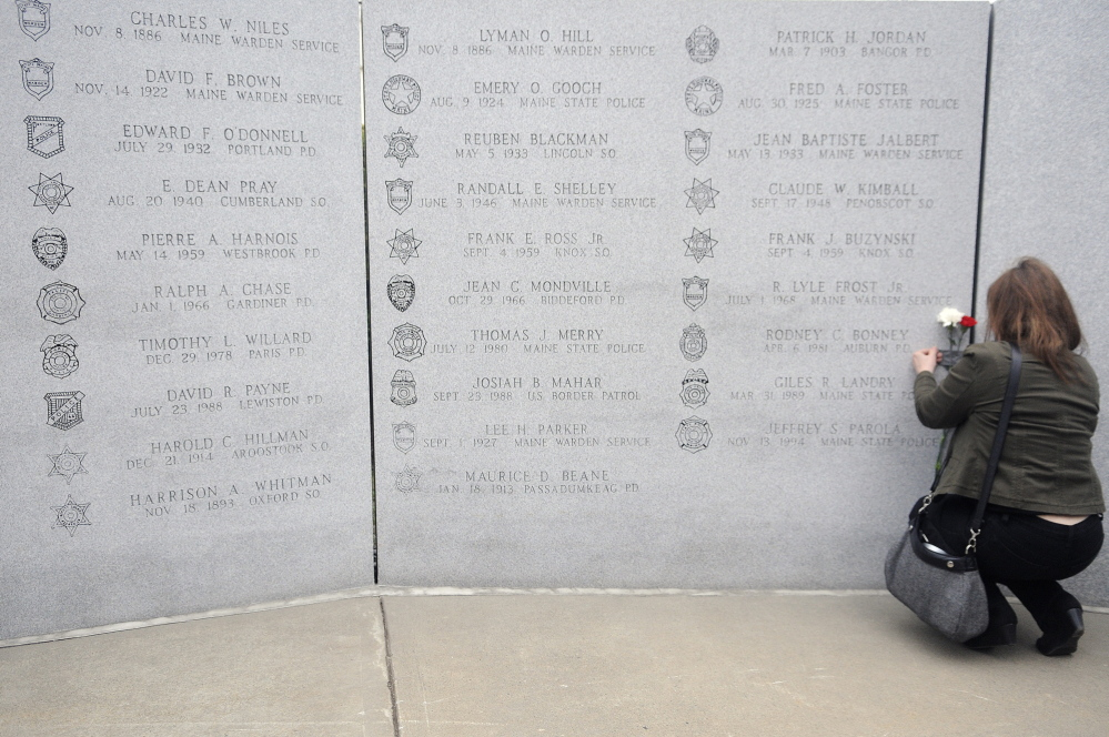 Remembered: Cherrie Bonney tapes flowers next to the name of her husband, Rodney Bonney, inscribed on the Maine Law Enforcement Officers Memorial during a service Thursday in Augusta. Auburn Police Officer Rodney Bonney drowned April 6, 1981, attempting to save a teenage boy who fell into the Androscoggin River.