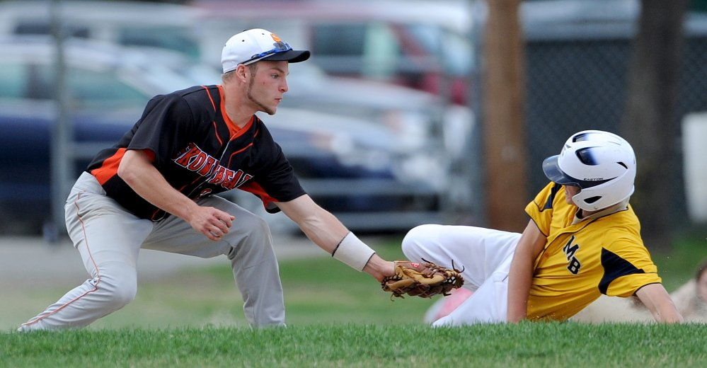 Staff photo by Michael G. Seamans NO STEALING: Skowhegan High School's Ben Salley, 21, tags out Ritchie Storer, 5, on a steal attempt in Farmington on Friday.