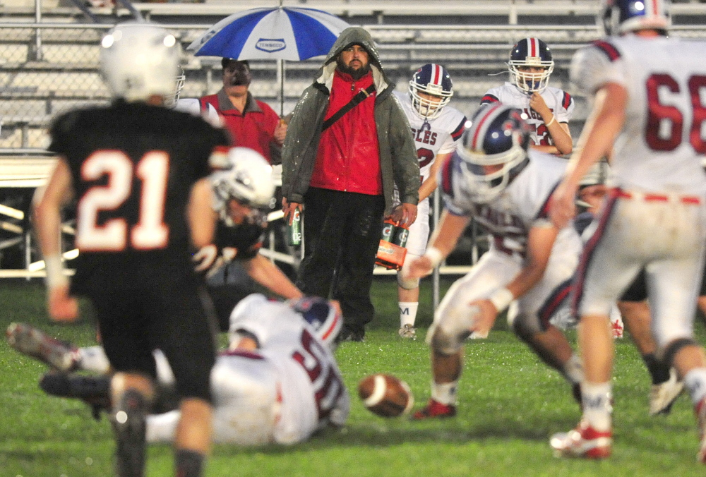 Watchful Eye: Messalonskee High School athletic trainer Nick Thompson, center, watches as Skowhegan Area High School battles for the ball with Messalonskee High School in the second quarter at Skowhegan Area High School Sept. 13, 2013.