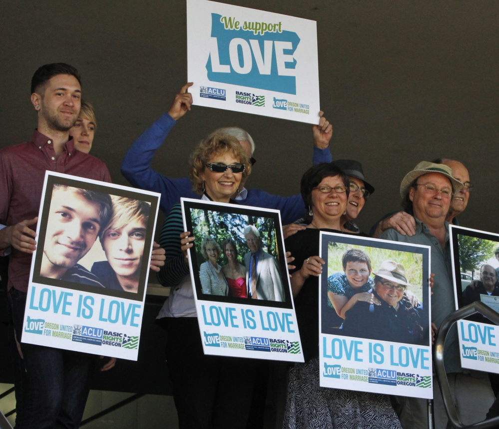 Supporters of same-sex marriage hold photos of themselves and their family members or partners on the steps of the Wayne L Morse U.S. Courthouse on May 14 in Eugene, Ore.