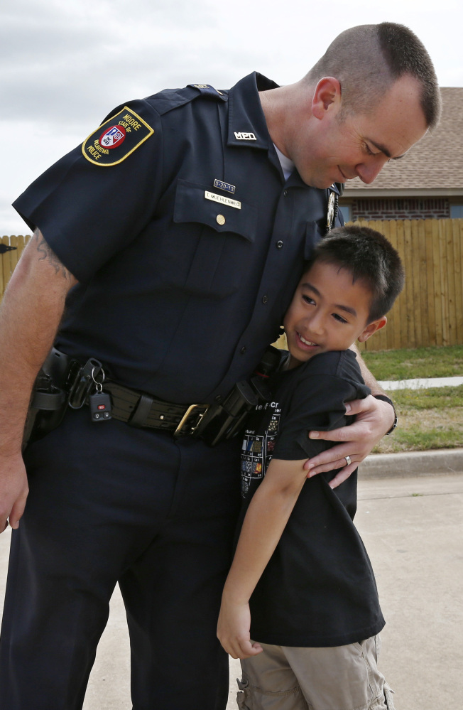 Moore police officer Travis Muehlenweg, left, hugs Kai Heuangpraseuth, as they meet in Moore, Okla. Last year, Muehlenweg was photographed pulling Heuangpraseuth from the rubble of the school. Heuagpraseuth's mother, Jacalyn Russell, said her son has wanted to meet Muehlenweg for nearly a year.