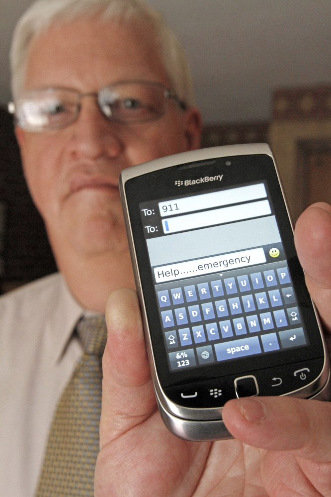 In this April 18, 2012, file photo, David Tucker, executive director of Vermont's Enhanced 911 Board, holds a smart phone in Montpelier, Vt. Tucker says the state is the first in the country where customers of the four major wireless carriers can send text messages to 911.