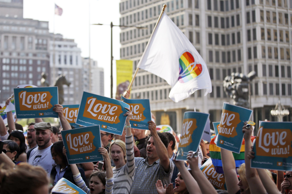 People hold up signs and cheer during a rally at Philadelphia City Hall on Tuesday.