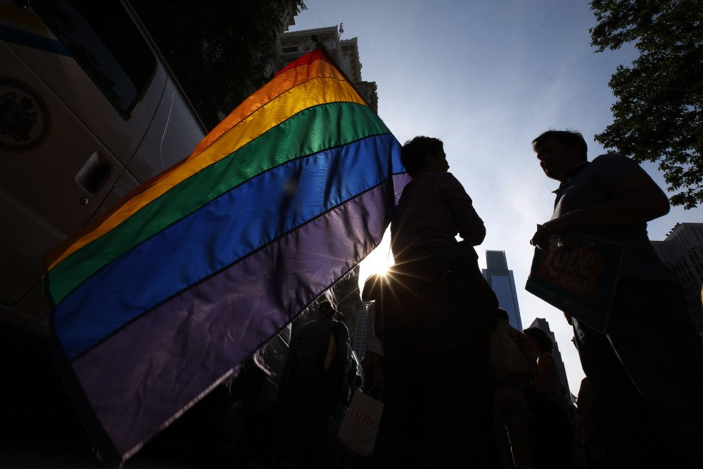 A person holds a flag during a rally at Philadelphia City Hall on Tuesday. Pennsylvania's ban on gay marriage was overturned by a federal judge Tuesday.