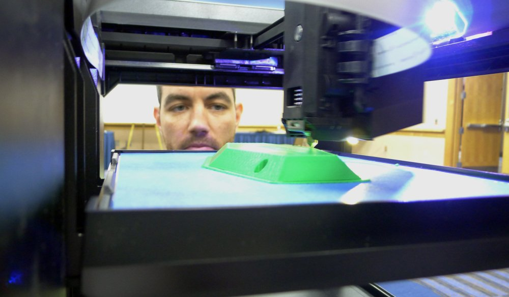 Michael Fieldson watches a 3D printer making an object during a trade show in Tampa, Fla.