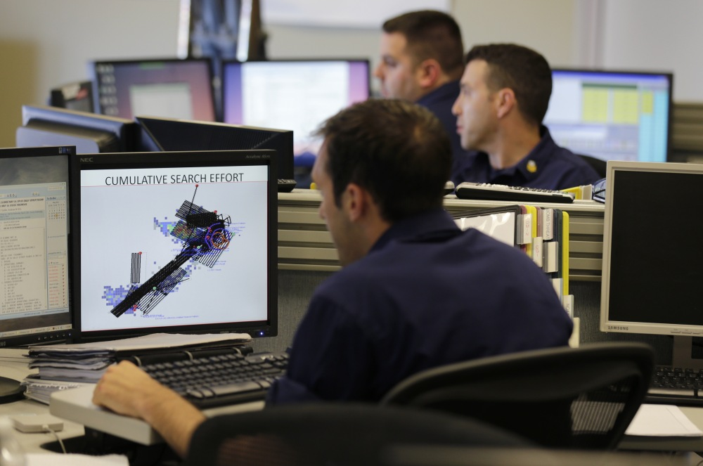 Operations unit controllers at the command center at the U.S. Coast Guard district headquarters in Boston check search pattern maps while trying to find the Cheeki Rafiki and its crew off the coast of Massachusetts.