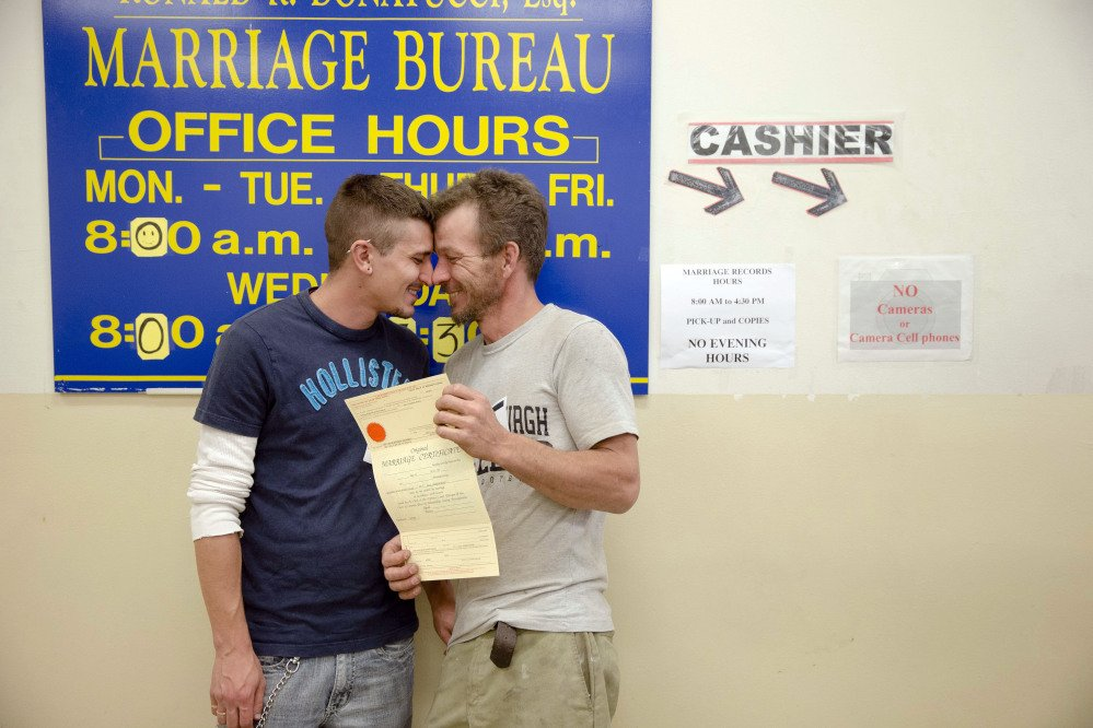 William Roletter, left, and Paul Rowe, press close to each other after they having their photo taken for their marriage certificate on Wednesday at City Hall in Philadelphia. On Tuesday, Pennsylvania became the final Northeastern state and the 19th in the U.S. to legalize same-sex marriage.