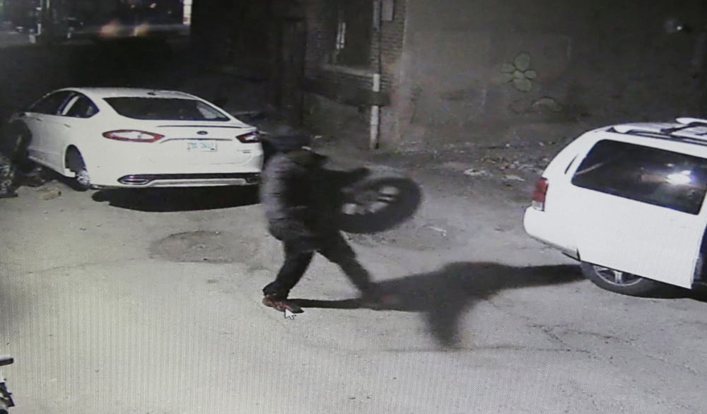 In an image from video provided by the Detroit police, car thieves take the tires off a Ford Fusion. Detroit police reported 720 carjackings last year in the city of 700,000 people.