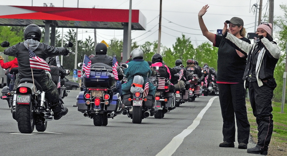 STONE POSSE: Michelle Moen, left, of Cape Elizabeth, and Brenda Smith, of Seabrook, N.H., wave as the Patriot Guard Riders pull away after a stopover by The Summit Project convoy on Friday at the West Gardiner rest area off the Maine Turnpike.