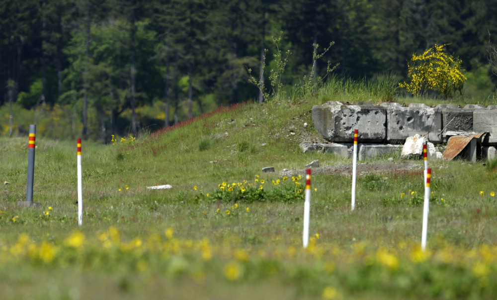 Markers near a bullet-pocked bunker designate a restricted area Joint Base Lewis McChord, Wash.
