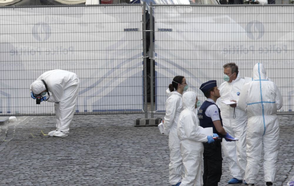 Forensic experts examine the site of a shooting at the Jewish museum in Brussels on Saturday. Belgian officials say that at least three people have been killed in gunfire at the Jewish Museum in Brussels.