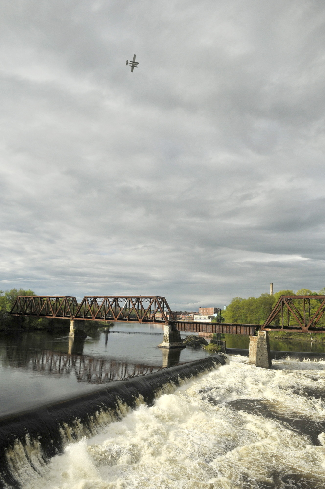 Eyes in the sky: A search plane from the Warden's service scans the Kennebec River Saturday for a reported missing person. Police were told a teenage girl or woman left her clothing folded on the riverbank with her shoes and was not seen again.