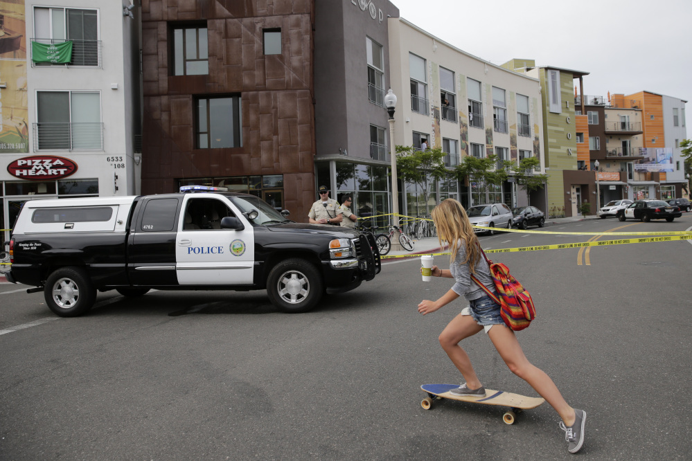 A woman rides her skateboard past the scene of a shooting on Saturday in Isla Vista, Calif. A drive-by shooter went on a rampage near a Santa Barbara university campus that left seven people dead, including the attacker, and others wounded, authorities said Saturday.