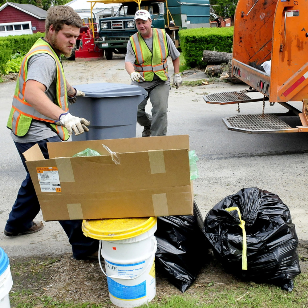 PAY UP: Waterville Public Works employees Larry Colson, left, and Brian Ames pick up city trash on Thursday, May 22, 2014. There are strong opinions on the subject of the pay-as-you-throw system the city is moving toward adopting.