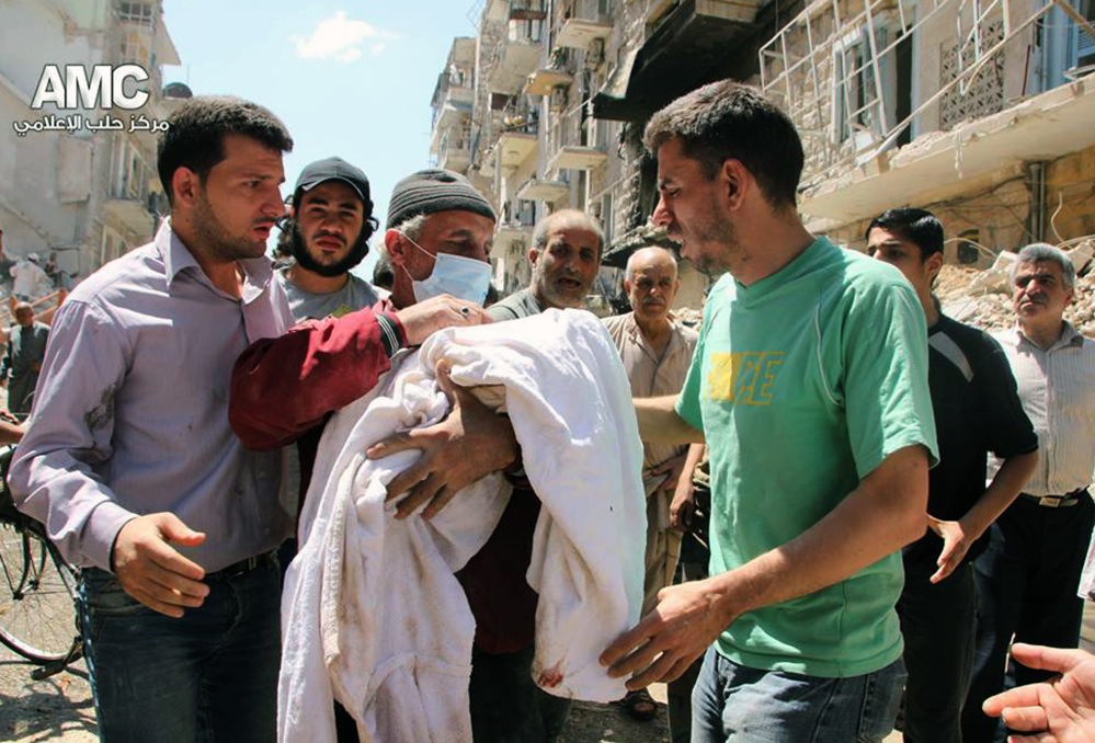 In this photo provided by the anti-government activist group Aleppo Media Center, which has been authenticated based on its contents and other AP reporting, shows a Syrian man, center, carrying the body of a victim of a Syrian government airstrike, in Aleppo, on Monday.