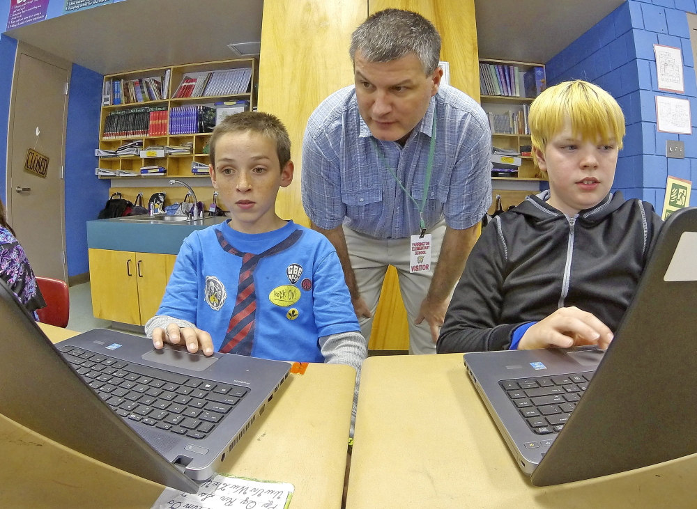 UPGRADE: Tony Paine, CEO of Kepware Technologies, center, chats with fourth-graders Gabriel Biasuz, left, and Jared Barker about how they use the laptops, that his company donated to the class earlier in the year, during a visit on Friday at Farrington School in Augusta.