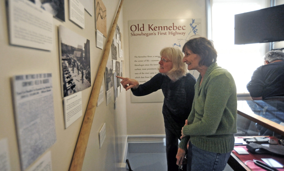 EXHIBIT: Mary Stuart points to a picture for Maureen Calder of the Old Kennebec, Skowhegan's first highway, at an exhibit highlighting the piece of local history at The Skowhegan History House Museum & Research Center on Wednesday.