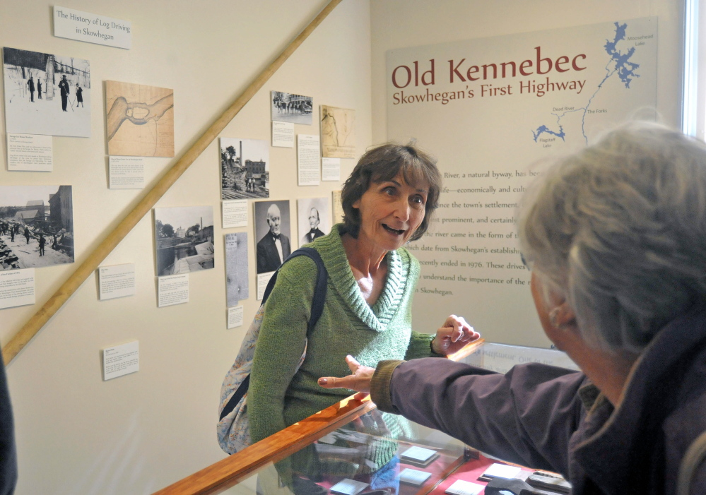 "LOG DRIVE HISTORY: Maureen Calder, center, takes in the exhibit of The Skowhegan History House Museum & Research Center's exhibit ""Old Kennebec - Skowhegan's First Highway"" on Wednesday."