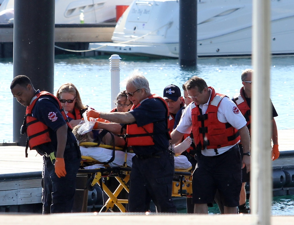 A woman is rescued from the South Side stretch of Lake Michigan, Sunday, after a boat she was in capsized Saturday night miles from Chicago's shoreline.