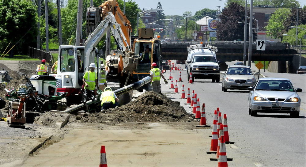 DIRTY WORK: Contractors install the natural gas pipeline on College Avenue in Waterville on Tuesday.
