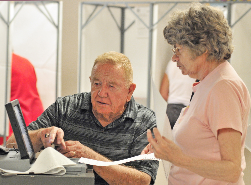 Staff Photo by Joe Phelan VOTING: Buzz Knight, left, helps resident Jackie Grenier feed her ballots into the machine Tuesday in Cumston Hall in Monmouth.