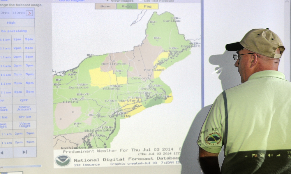 Central Maine Pyrotechnics proprietor Steve Marson checks the weather Thursday while rescheduling fireworks shows his company was scheduled to shoot on the Fourth of July. Marson observes changes in the weather from several computer monitors at his Farmingdale office to determine how to plan shows.