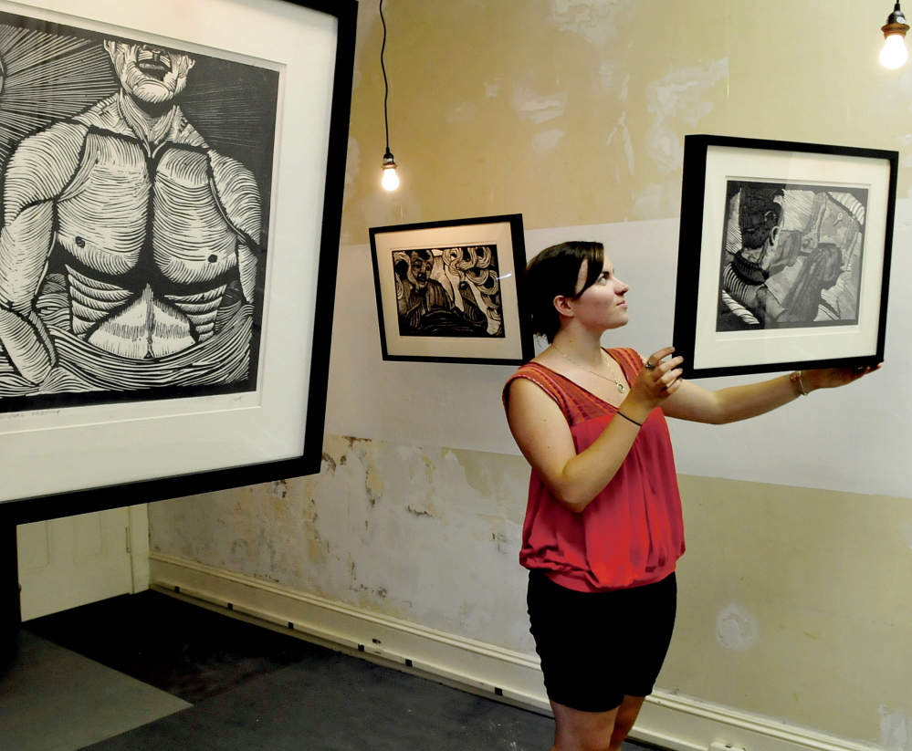 Rachel McDonald, program manager at Common Street Arts in Waterville Monday, hangs artwork that will be part of the Waterville Arts Festival event that is running in conjunction with the Maine International Film Festival this Saturday.