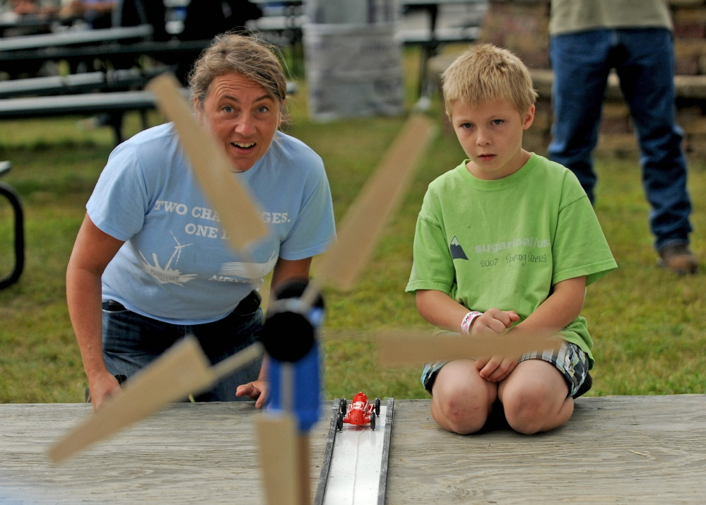 Tanner Mayo, 9, of Temple, learns about wind power on Friday, Aug. 15, 2014, from Lisa Twombly, Maine Wind Blade Challenge coordinator, an event sponsored by Wind for Maine and the Maine Ocean and Wind Industry Initiative at the Skowhegan State Fair.