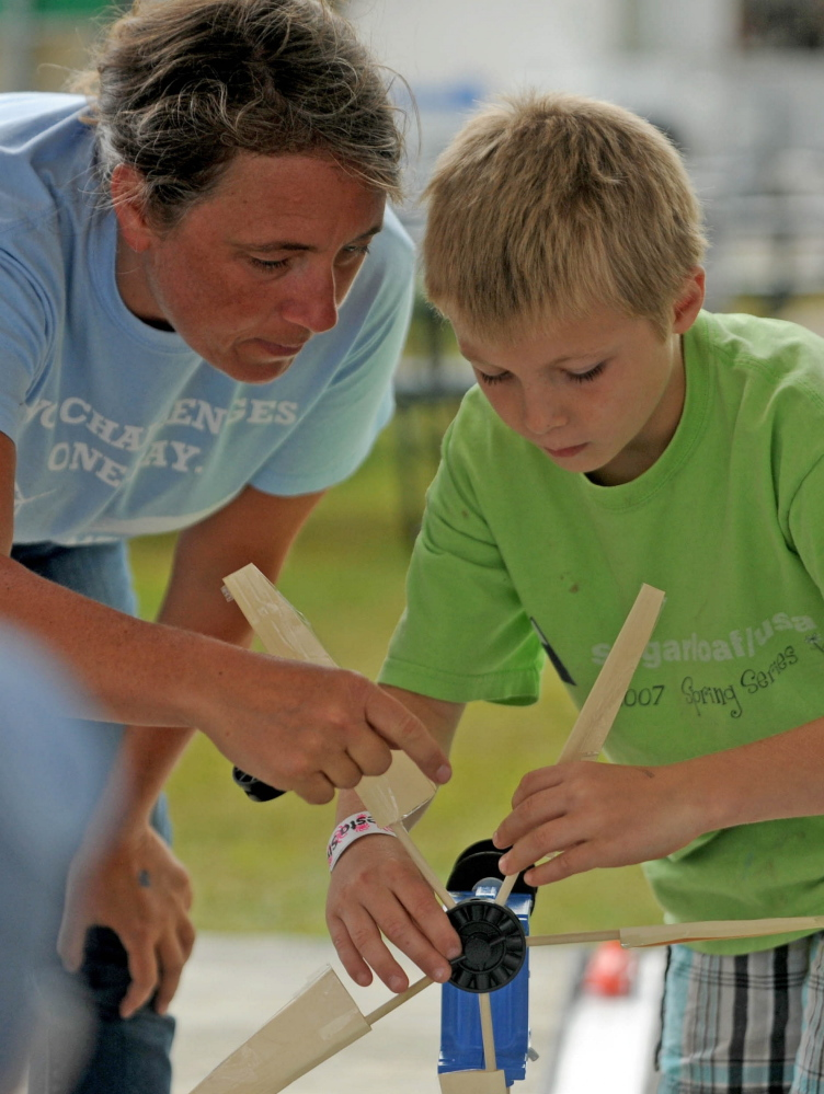 Tanner Mayo, 9, of Temple, builds a wind mill to power a toy car with the help of Lisa Twombly, Maine Wind Blade Challenge coordinator. The event was sponsored by Wind for Maine and the Maine Ocean and Wind Industry Initiative at the Skowhegan State Fair on Friday.